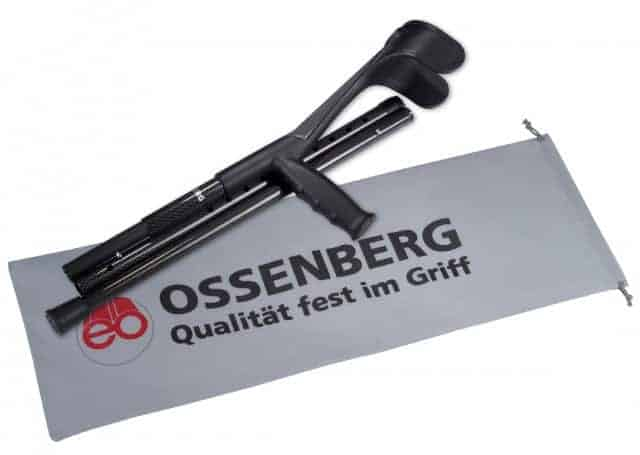 Image shows the black Oseenberg crutch folded neatly on top of a small white fabric carry pouch, printed with the Ossenberg logo